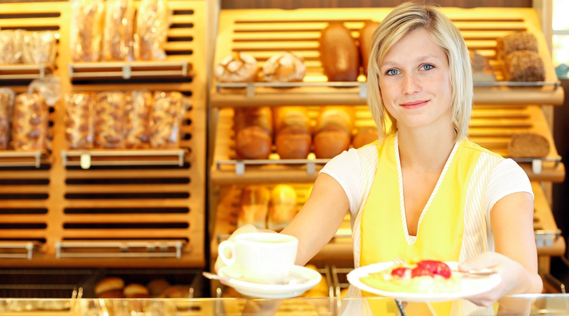 Image of woman in yellow apron smiling and offering baked goods from behind the counter of the business