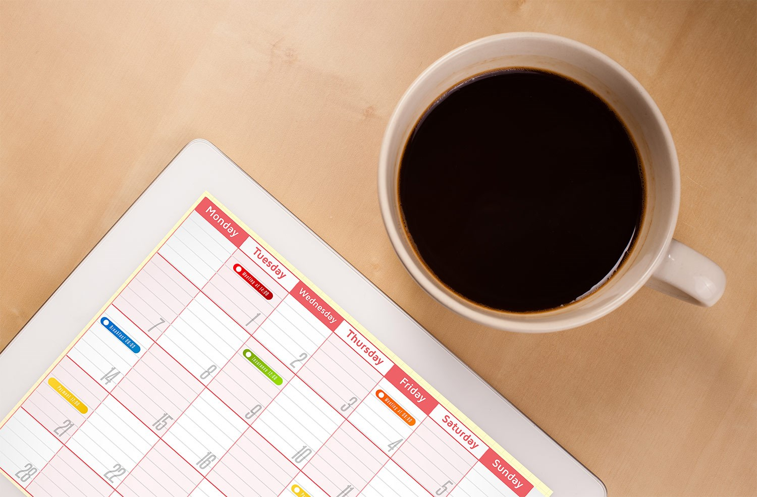 Image of coffee cup filled with coffee sitting on desk next to calendar with days of the month and different colors coded on each day.
